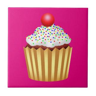 Le petit gâteau avec arrose et cerise sur le petit carreau carré