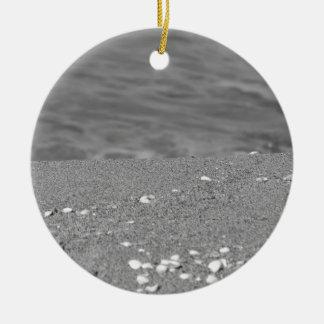 Le plan rapproché de la plage de sable avec la mer ornement rond en céramique