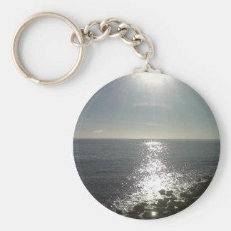 le soleil se levant au-dessus de la mer porte-clé rond