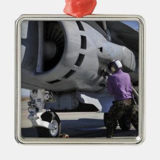 Le technicien de carburant d'aviation attache un ornement carré argenté