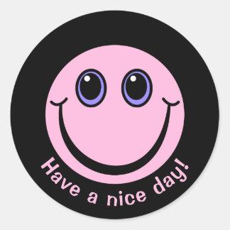 Le visage souriant rose ont un beau jour sticker rond