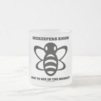 Les apiculteurs savent à l'abeille pendant le mug en verre givré