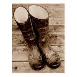 Les bottes en caoutchouc boueuses d'un agriculteur carte postale
