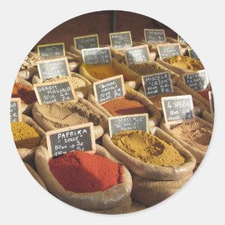 Les épices colorées dans le jute met en sac au sticker rond