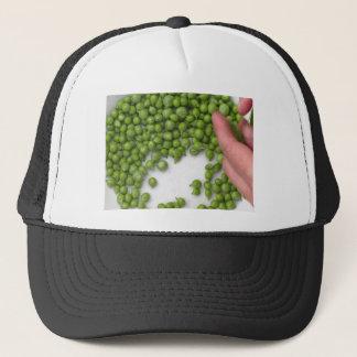 Les mains de femme écossent les pois d'un plat casquette
