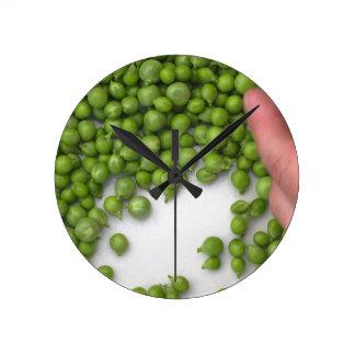 Les mains de femme écossent les pois d'un plat horloge ronde