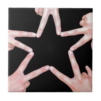 Les mains des filles faisant l'étoile forment sur petit carreau carré