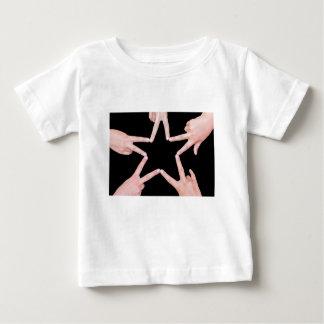 Les mains des filles faisant l'étoile forment sur t-shirt pour bébé