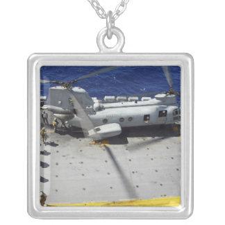 Les marines montent à bord d'un hélicoptère de pendentif carré