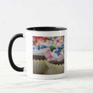 Les petits gâteaux de chocolat avec le glaçage et mug