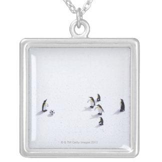 Les pingouins jouant au football pendentif carré
