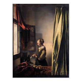 Lettre de lecture de fille à la fenêtre ouverte carte postale