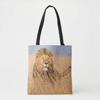 Lion masculin caché dans l'herbe tote bag