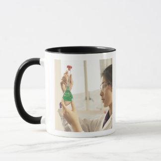 Liquide de examen de scientifique dans le becher mug