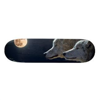 Loups de loup hurlant à la pleine lune planche à roulette