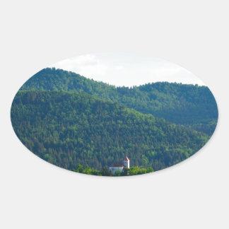 Lumière d'après-midi au-dessus d'église sticker ovale