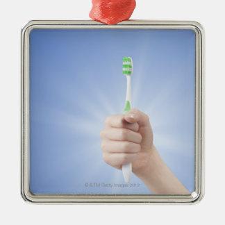 Main tenant la brosse à dents ornement carré argenté