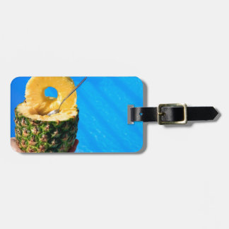 Main tenant l'ananas frais au-dessus de la piscine étiquette à bagage