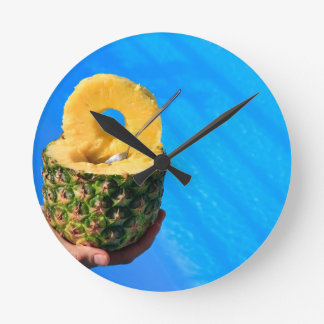 Main tenant l'ananas frais au-dessus de la piscine horloge ronde