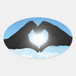 Mains en silhouette de forme de coeur sur le ciel sticker ovale