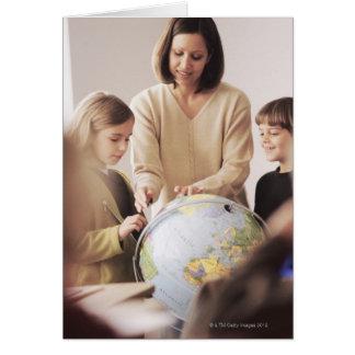 Maître d'école élémentaire montrant le globe à carte de vœux