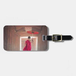 Moine bouddhiste avec le parapluie rouge étiquette à bagage