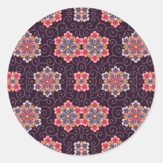 Motif de fleur coloré sur le pourpre foncé sticker rond