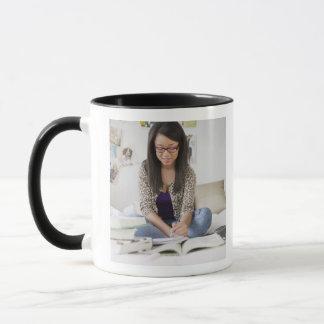 Mug Adolescente de métis faisant le travail sur le lit