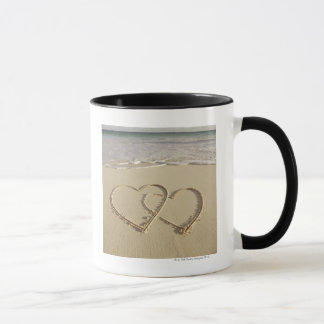 Mug Deux coeurs sus-jacents dessinés sur la plage avec