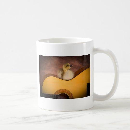 Mug little goose on a guitar