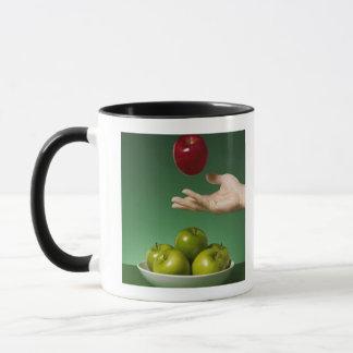 Mug remettez jeter la pomme rouge à l'air et en le