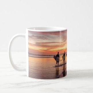 Mug Surfers au coucher du soleil marchant sur la
