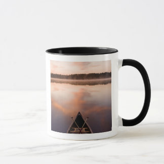 Mug Un canoë se repose sur le rivage du lac