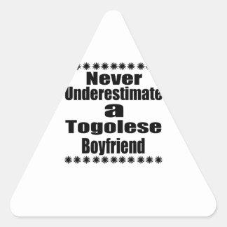 Ne sous-estimez jamais un ami togolais sticker triangulaire