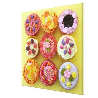 Neuf petits gâteaux chacun décoré de la sucrerie toiles