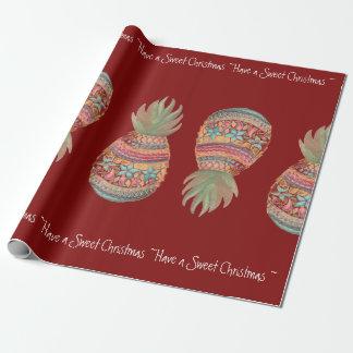 Noël doux d'ananas enveloppant le rouge papier cadeau