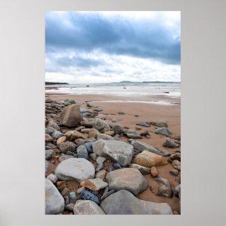 nuages de tempête au-dessus de plage beal rocheuse posters