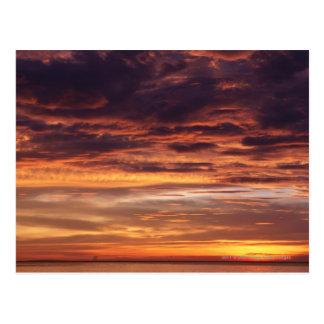 Nuages foncés en ciel strié par orange carte postale