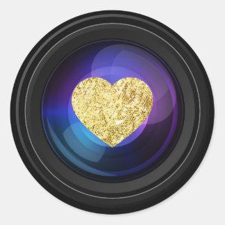 Objectif de caméra de photographe avec le coeur sticker rond