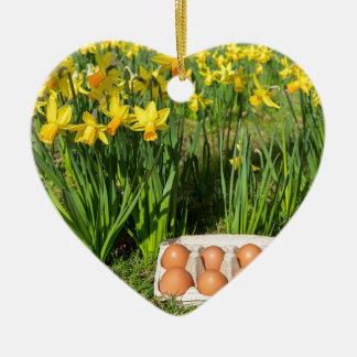 Oeufs dans la boîte sur l'herbe avec les ornement cœur en céramique