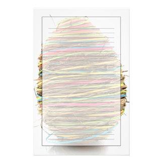 Oeufs de pâques colorés de paille au-dessus de bla papier à lettre customisable