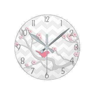 Oiseau gris rose sur l'horloge murale de branche horloge ronde