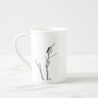 Oiseau sur une tasse de porcelaine tendre de