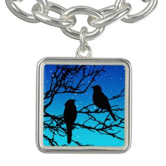 Oiseaux sur une branche, noire contre même le bleu bracelets