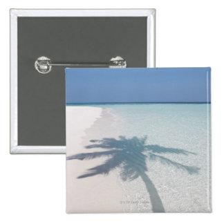 Ombre d'un palmier sur une plage abandonnée d'île badges