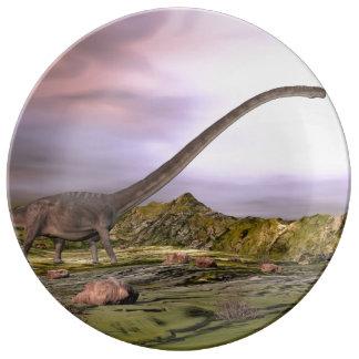 Omeisaurus marchant dans le désert par coucher du assiettes en porcelaine