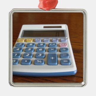 Ornement Carré Argenté Calculatrice solaire sur une table en bois