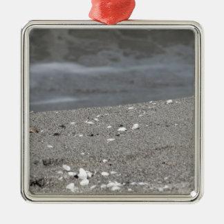 Ornement Carré Argenté Le plan rapproché de la plage de sable avec la mer