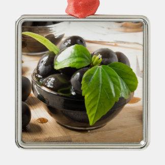Ornement Carré Argenté Olives noires sur une table et des tasses en verre