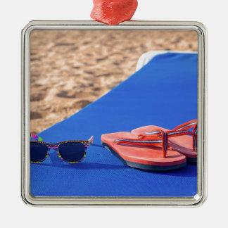 Ornement Carré Argenté Pantoufles et lunettes de soleil sur le lit pliant